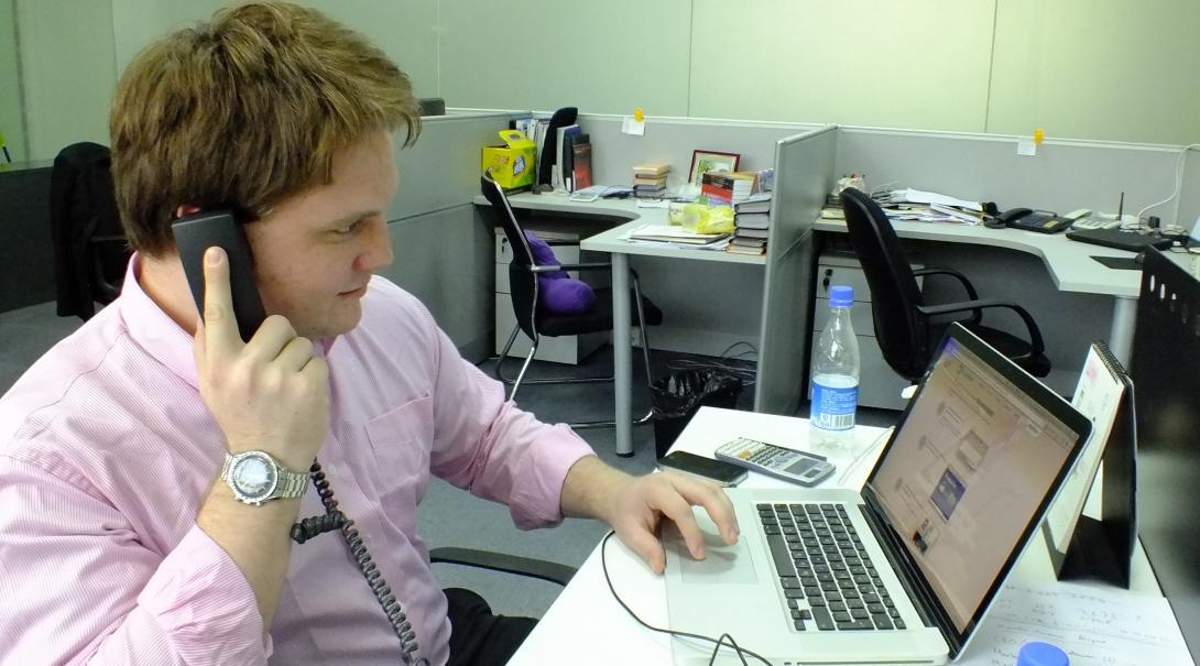 Male business intern sits at a desk on the phone in a marketing office during his internship in China.